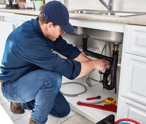 Plumber working under a kitchen sink